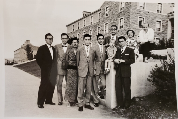group of people in a black and white photo posing around a half wall in front of a building